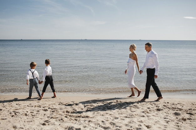 Stylish family is walking on the beach near the calm sea, parents and children are holding hands together