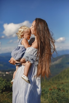 Stylish family in the mountains. mom and daughter on a sky background. woman in a white dress.
