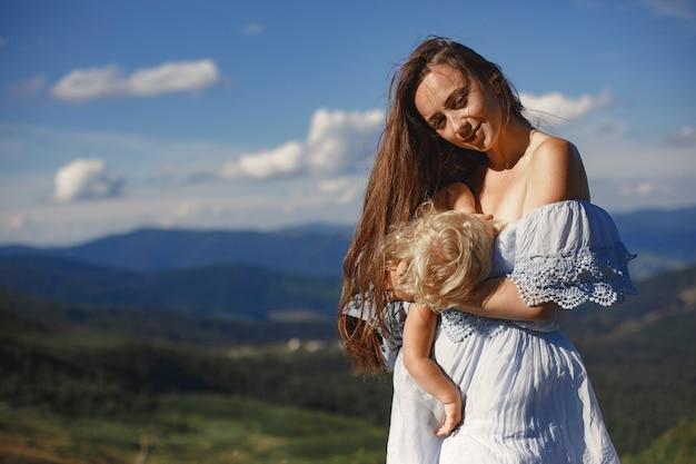 Elegante famiglia in montagna. mamma e figlia su uno sfondo di cielo. donna in abito bianco.