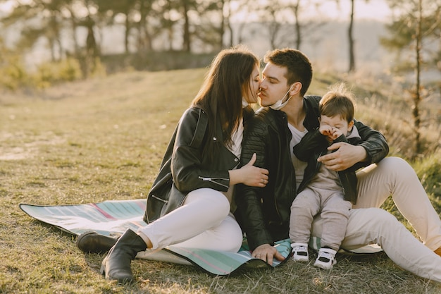 Stylish family sitting on a spring field