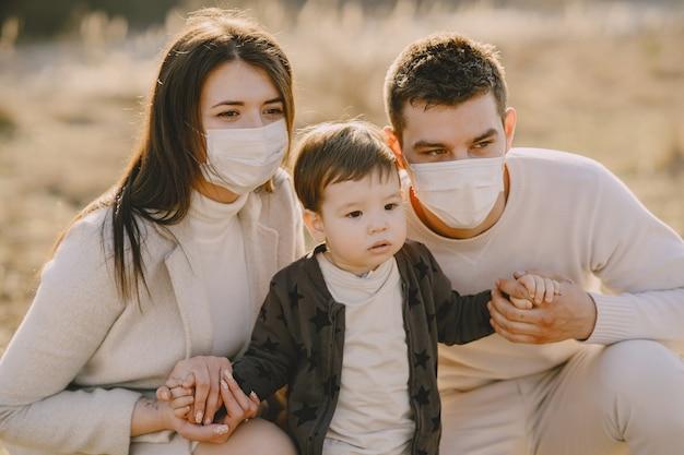 春の野原の上を歩くマスクを身に着けているスタイリッシュな家族