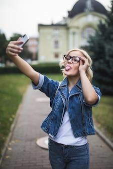 Стильная модная блондинка в джинсовом костюме и очках делает селфи на своем телефоне в городе утром