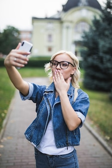 청바지 스위트의 세련된 패션 금발 소녀 여자가 아침에 도시에서 그녀의 전화에 셀카를 제공합니다
