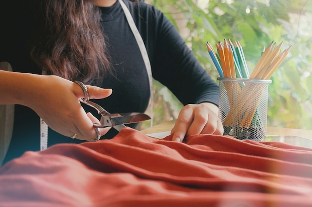 Stylish fashion designer cutting fabric of new collection in atelier. creative design concept.