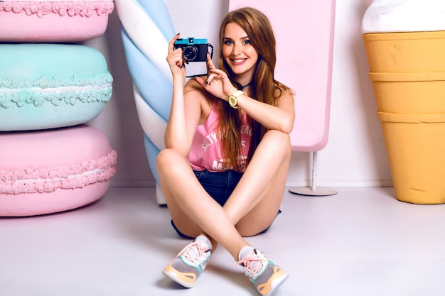 Stylish fashion portrait of cheerful young woman sitting on the floor, smiling and taking photo on camera. happy emotions. positive mood. bright colorful lifestyle