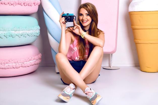床に座って、笑顔でカメラで写真を撮る陽気な若い女性のスタイリッシュなファッションの肖像画。幸せな感情。ポジティブな気分。明るくカラフルなライフスタイル
