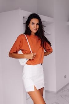 Стильная модная молодая кавказская женщина-блоггер дома в спальне в рубашке и юбке кирпичного цвета