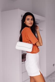 レンガ色のシャツとスカートを身に着けている寝室で自宅でスタイリッシュなファッションの若い白人女性ブロガー