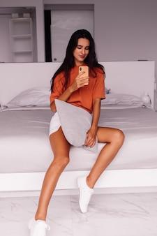 Elegante moda giovane donna caucasica blogger a casa che cattura foto