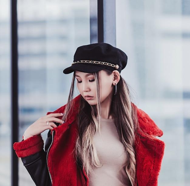 赤い毛皮のジャケットでスタイリッシュなファッショナブルなアジアの女の子