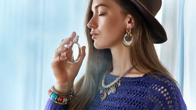 Stylish fashionable attractive brunette boho chic woman with closed eyes wearing jewelry and hat holds perfume bottle