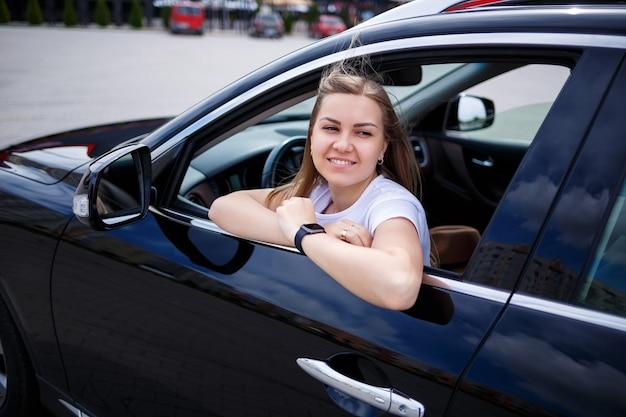 黒のビジネスクラスの車のサロンに座っているスタイリッシュでファッショナブルな美しい少女。彼女の顔に笑顔の若い女性。駐車場の女性