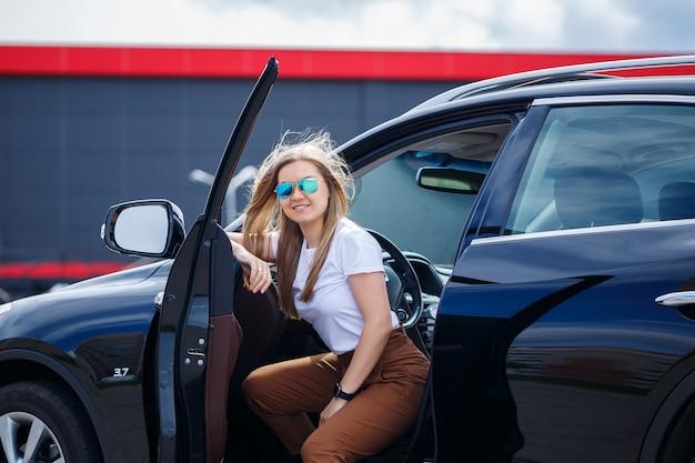 黒のビジネスクラスの車のサロンに座っているスタイリッシュでファッショナブルな美しい少女。彼女の顔に笑顔の若い女性。