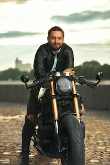 Stylish fashionable biker dressed in a black leather jacket sitting on his motorcycle, looking at camera.