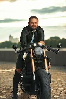 Стильный модный байкер, одетый в черную кожаную куртку, сидит на своем мотоцикле и смотрит в камеру.