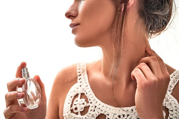 白い壁に香水瓶スプレーでスタイリッシュなおしゃれなブルネットの女性