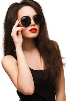 サングラスを身に着けている黒い服を着たスタイリッシュなファッショナブルなブルネットの少女。