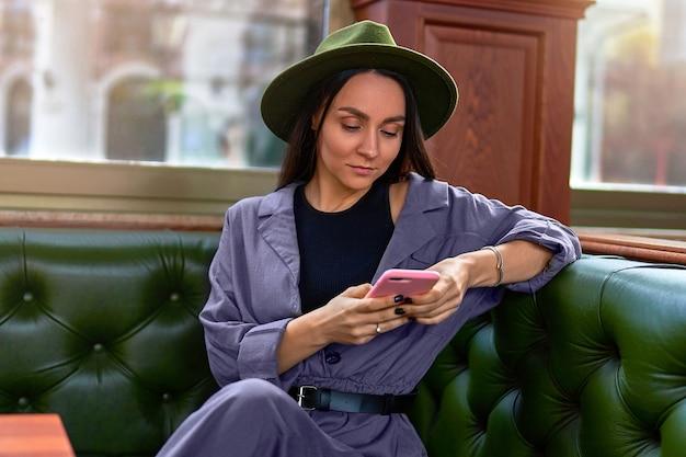 Стильная модная элегантная милая привлекательная битник женщина-путешественница с помощью телефона