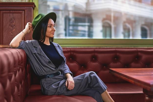 Стильная модная элегантная задумчивая задумчивая хипстерская женщина-путешественница сидит в одиночестве у окна в кафе-магазине