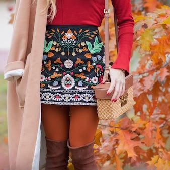 Stylish and fashionable girl in autumn foliage. autumn trend