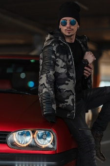 Stylish fashionable man with sunglasses and a hat in a military jacket and jeans standing by a red car in the parking lot