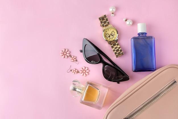 Стильная модная розовая сумка и женская косметика и аксессуары на ярком модном розовом фоне. женский аксессуар концепции. вид сверху