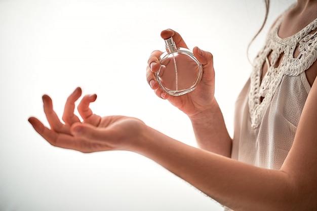 白い壁に手首のお気に入りの香水の香りに適用する白いブラウスでスタイリッシュなおしゃれなトレンディな女性