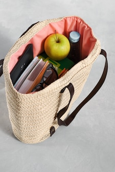 Stylish fashionable wicker bag with textbooks and notebooks