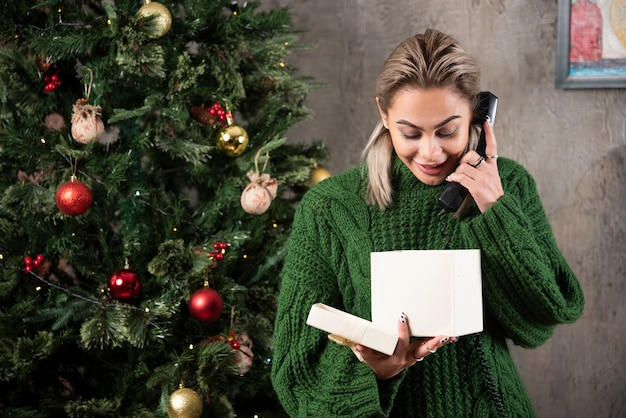 Stylish fashionable woman in green sweater speaking on telephone