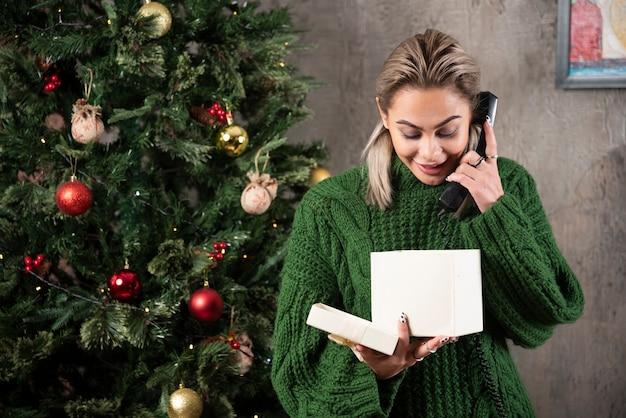 전화에 말하는 녹색 스웨터에 세련 된 유행 여자