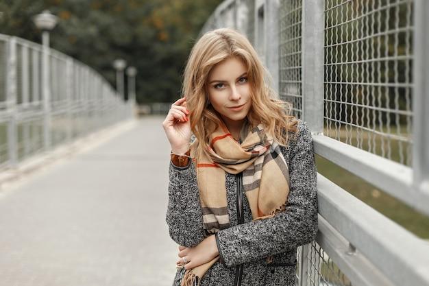 Стильная модная женщина в винтажной одежде возле металлического забора
