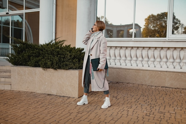エレガントなスタイルのコートで通りを歩くスタイリッシュなファッショナブルな女性