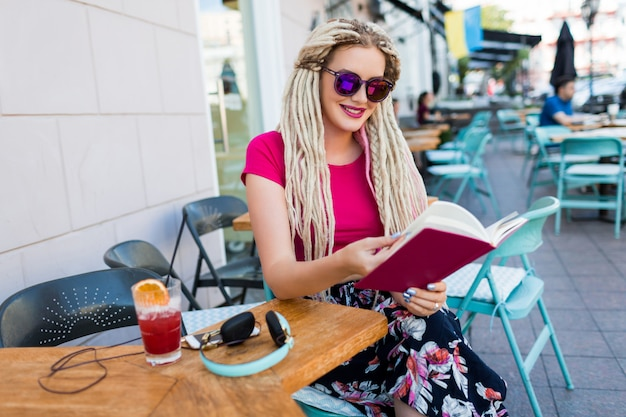 Stylish fashionable woman with white dreadlocks in sunglasses holding notebook and spending her free time in modern restaurant. fresh smoothie and earphones on table .