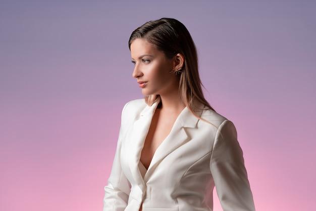 豪華な白いスーツを着たスタイリッシュでファッショナブルな若い女性