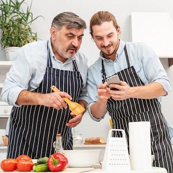 Стильный отец и сын смотрят на телефон
