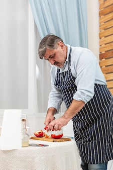 Stylish father cutting tomatoes