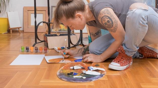 Stylish female artist painting woman portrait sitting on floor