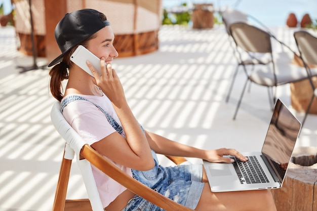 Stylish female in black cap, casual white t shirt, messages in online chat on laptop computer, talks with best friend on smart phone