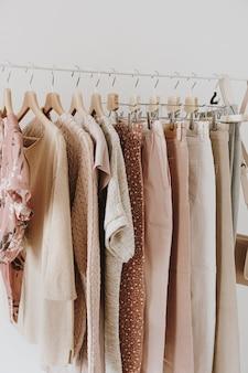 白のハンガーにスタイリッシュな女性のブラウス、セーター、パンツ、ジーンズ、tシャツ