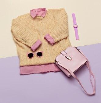 세련된 여성복 세트입니다. 세련 된 배경에 여자/소녀 복장입니다. 핑크색. 핸드백, 선글라스, 시계. 스웨터와 셔츠 평면 위치, 평면도.