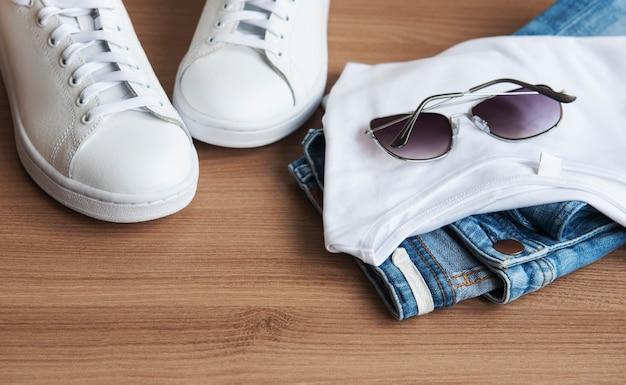 Комплект стильной женской одежды. наряд женщины на деревянных фоне. концепция покупок в интернете. доставка одежды.