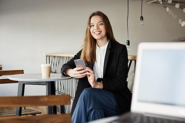 携帯電話でカフェに座っているスタイリッシュな女性起業家、笑みを浮かべて