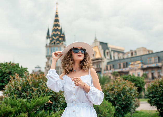 Stylish female girl in white dress discovering and traveling alone in europe