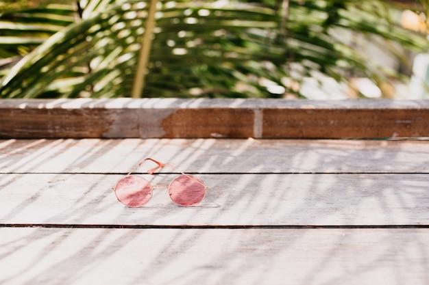 木製のテーブルの上に横たわるスタイリッシュな女性のメガネ。 無料写真