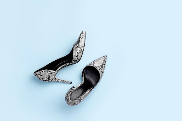 青い背景のスタイリッシュな女性のハイヒールの靴。フラットレイ、上面図。