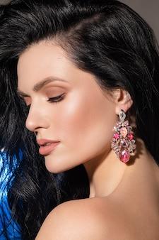 スタイリッシュな女性のジュエリー。完璧なメイクで輝きのイヤリングを身に着けている美しいブルネットの女性の肖像画を閉じます。