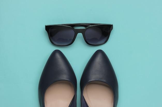 Стильный женский образ кожаные туфли на каблуках и солнцезащитные очки на синем фоне