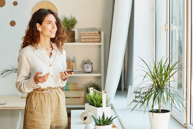 Stylish female manager telling something to her colleagues using smartphone during online meeting