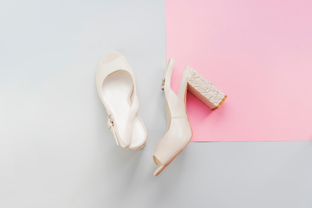 Stylish female milk colored wedding heel shoes isolated on blue and pink background.