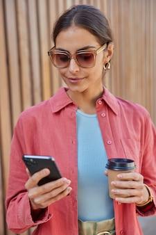 Stylish female model holds mobile phone reads notification uses online navigator to find right direction connected to fast internet in roaming drinks takeaway coffee wears sunglasses pink shirt